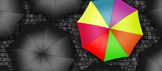 Many colors umbrella. Bright umbrella among set of black umbrell